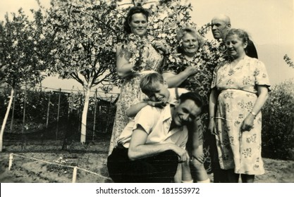 GERMANY, ROSTOCK - CIRCA 1950s: An antique photo of family posing in the blossoming garden