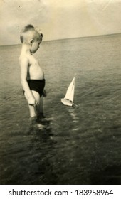 GERMANY, ROSTOCK - CIRCA 1950s: An antique photo of little boy playing with toy boat on the sea beach, Rostock