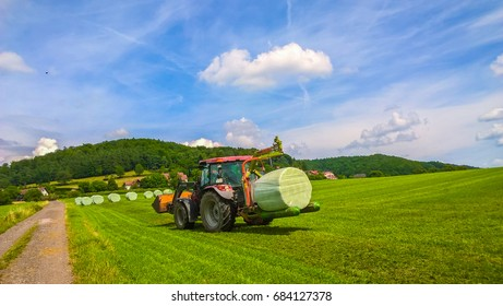 Germany, Schollkrippen village-June,14. 2017. Yellow cylinders of mowed grass will soon be packed in film, that keeps all nutritious qualities. Yet cylinders are dried on the field for some more days