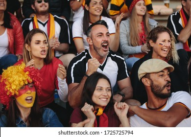 Germany soccer team supporters having great fun watching a live match from stands. People sitting in fan zone watching match and cheering.
