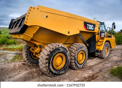 Germany, Spiekeroog: Big yellow Caterpillar dumper at a building site - model Cat 730C2 three axle articulated truck - concept industry building site business dumping boom vehicle. August 17, 2018