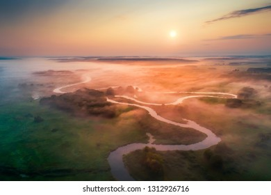 Germany. Spring colorful landscape. Green meadow with mist and river aerial drone view. Bright sun paints fog with red and yellow colors.
