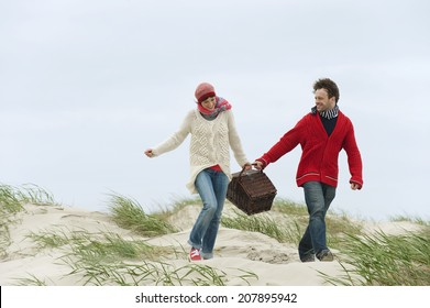 Germany St.Peter-Ording North Sea couple holding picnic basket walking on beach