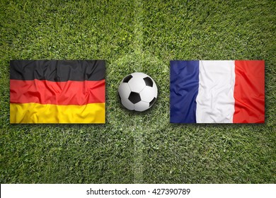 Germany vs. France flags on a green soccer field