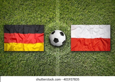 Germany vs. Poland flags on green soccer field