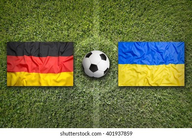Germany vs. Ukraine flags on green soccer field