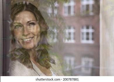 Germany, Woman looking out the window smiling