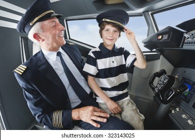 Germany,Bavaria,Munich,Senior pilot and boy in airplane cockpit