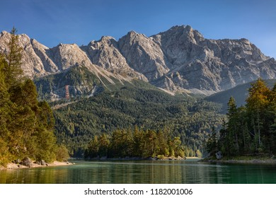 """Germanys highest mountain called """"Zugspitze"""" with part of the lake callled """"Eibsee"""" in the foreground"""
