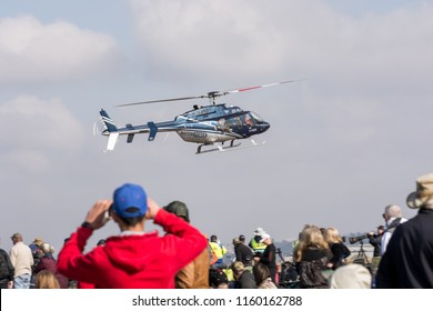 Germiston, South Africa - August 19, 2018: Bell 407 Helicopter display at the 2018 Rand Airshow while spectators watch
