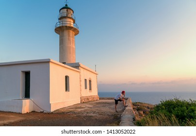 Gerogompos lighthouse on Kefalonia island, young man is looking at the sunset