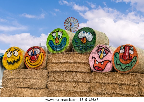 Gervais, Oregon - September 24, 2019: Farm hay bales painted in funny faces for Halloween and windmill in the background.
