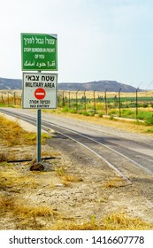 Gesher, Israel - June 04, 2019: The Jordan River valley, and border warning signs, near the border between Israel and Jordan