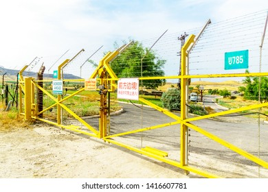 Gesher, Israel - June 04, 2019: The Jordan River valley, and border gate with warning signs, near the border between Israel and Jordan, in Old Gesher site