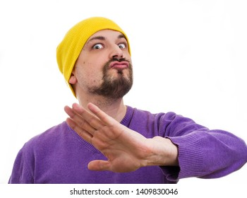 gesture of categorical denial. man in yellow hat and a purple sweater expressive make faces. humorous ironic funny male portrait on a white background.