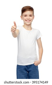 gesture, childhood, fashion, advertisement and people concept - happy smiling boy in white blank t-shirt showing thumbs up