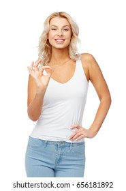 gesture, expressions and people concept - happy smiling young woman in white top and jeans showing ok hand sigh