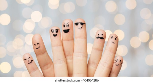 gesture, family, people and body parts concept - close up of two hands showing fingers with smiley faces over holidays lights background