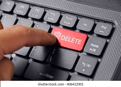 Gesture of a hand finger pressing DELETE on a laptop keyboard