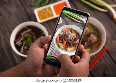 gesture of hand taking picture of delicious traditional food. blogger concept
