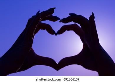 Gesture of the heart from the hands on the blurred sky