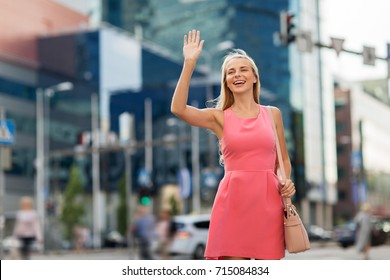 gesture, lifestyle and people concept - happy young woman waving hand on city street
