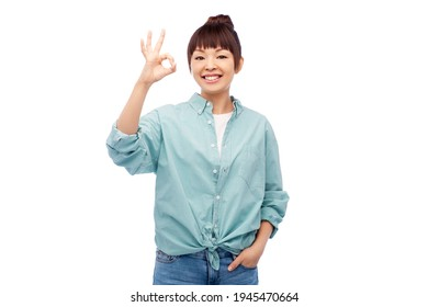 gesture and people concept - happy smiling young asian woman in cotton shirt r showing ok hand sign over white background
