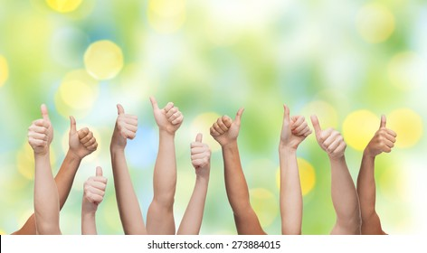 gesture, people, human race and international society concept - human hands showing thumbs up over green lights background