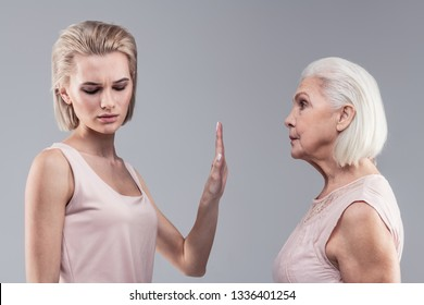 Gesture of silence. Categorical blonde woman shutting her mother up while resolutely raising hand