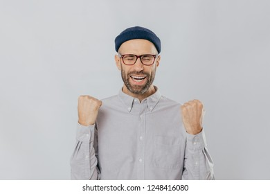 Gesture of success. Jubilant overjoyed unshaven man raises clenched fists, wears spectacles and formal shirt, celebrates his triumph, closes eyes from happiness, feels like real winner, isolated