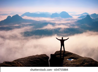 Gesture of triumph. Happy hiker in black.  Tall man on the peak of sandstone rock in national park Saxony Switzerland watching down to landscape.