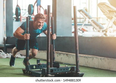 Get active. Athletic man exercising with a heavy training machine. Copy space on the right side