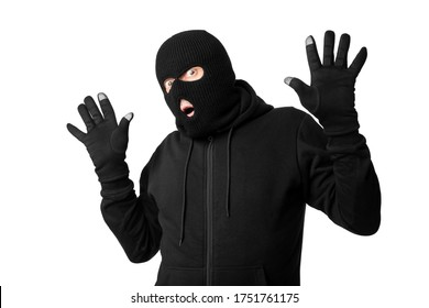 Get Caught Concept. Portrait of thief in black balaclava and gloves raising hands up, isolated over white studio background