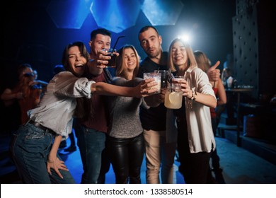Get crazy. Group of young friends smiling and making a toast in the nightclub.