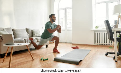Get Fit At Home. Full length shot of young active man watching online video training on laptop, exercising, stretching during morning workout at home. Sport, healthy lifestyle. Web Banner