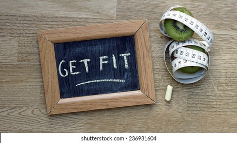 Get fit written on a chalkboard next to a kiwi an inches