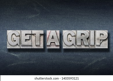 get a grip phrase made from metallic letterpress on dark jeans background