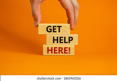 Get help here symbol. Male hand builds stack from blocks with words 'get help here'. Beautiful orange background. Copy space. Business and get help here concept.