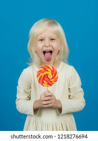 Get lost in the hypnotic swirl. Happy candy girl. Little girl hold lollipop on stick. Little child with sweet lollipop. Happy childhood food.