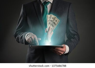 Get money online. Money cashback from internet store. Online payment or deal. Businessman with a tablet computer in hands and hand with cash.