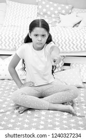 Get out of my room. Girl child sit on bed in her bedroom. Kid unhappy someone entered her bedroom bothering her. Girl kid long hair cute pajamas serious unhappy face. Get out of here pointing finger.