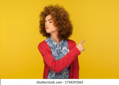 Get out! Portrait of upset vexed woman with curly hair showing exit, demanding to leave her alone, turning away with resentful irritated expression. indoor studio shot isolated on yellow background