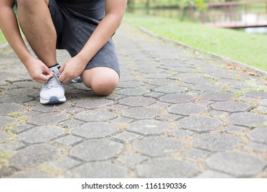 Get ready for exercise by checking your shoe rack and tightening it before running in the park.Exercise is a good health.Bend down to tie the shoe
