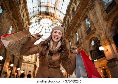 Get ready to making your way through shopping addicted crowd. Huge winter sales in Milan just started. Happy young woman with shopping bags in Galleria Vittorio Emanuele II rejoicing
