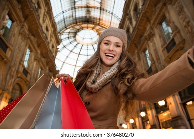 Get ready to making your way through shopping addicted crowd. Huge winter sales in Milan just started. Smiling young woman with shopping bags taking selfie in Galleria Vittorio Emanuele II