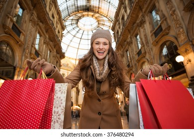 Get ready to making your way through shopping addicted crowd. Huge winter sales in Milan just started. Smiling young woman in Galleria Vittorio Emanuele II showing shopping bags