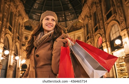 Get ready to making your way through shopping addicted crowd. Huge winter sales in Milan just started. Happy young woman with shopping bags standing in Galleria Vittorio Emanuele II and looking aside