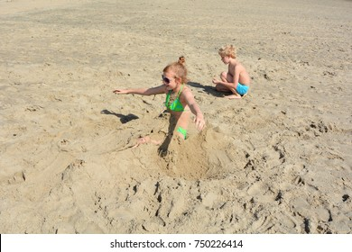 To get up in sand dug girl tried, boy sits besides