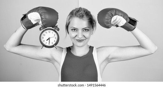 Get used to personal regime. Girl athlete boxing gloves and alarm clock. Sport lifestyle and healthy regime. Habits and regime concept. Improve yourself. Overcome harmful habits. Time for training.