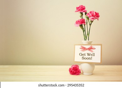 Get well soon message with pink carnations in a white vase